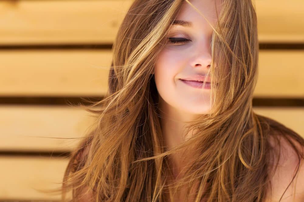 Eine Frau denkt positiv: Sie lächelt und blickt nach vorn.