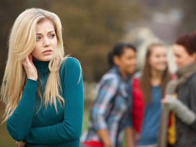 Eine Frau steht abseits von anderen Menschen. Sie fühlt sich unwohl.