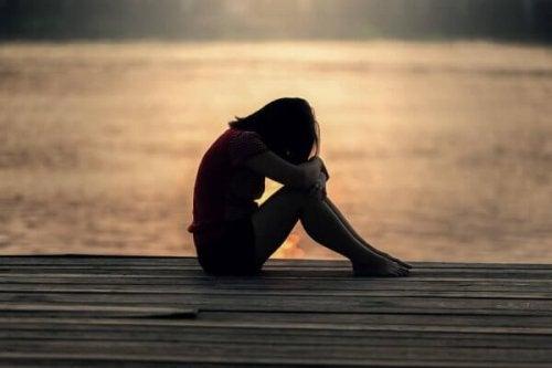 Frau sitzt allein auf Steg