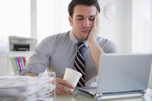 Erschöpfter Mann sitzt vor seinem Computer
