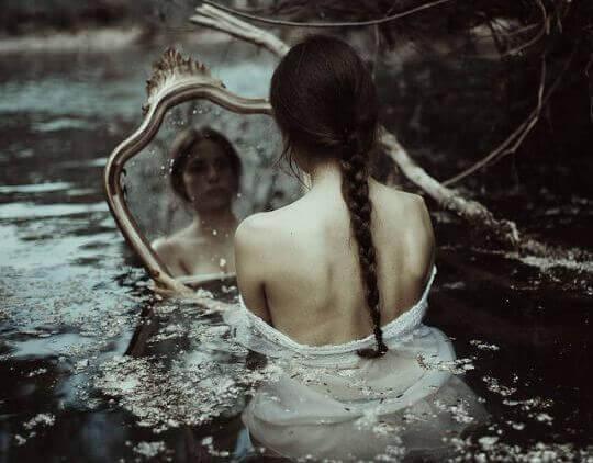 Frau betrachtet sich im Spiegel, das Wasser steht ihr bis zur Brust