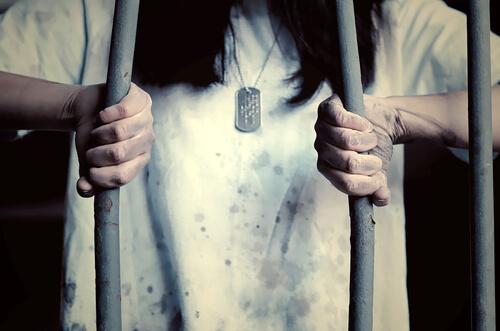 Eine Gefängnisinsassin biegt die Stäbe des Gitters auf.