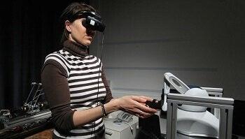 Eine Frau mit verbundenen Augen bedient einen Roboter.