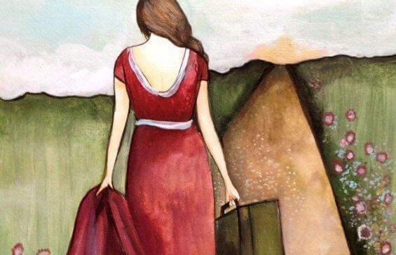 Frau läuft mit Koffer einen Weg entlang