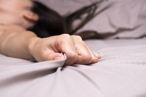 Frau hält sich am Bettlaken fest
