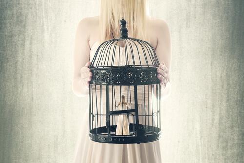 Eine Frau hält einen Vogelkäfig in den Händen, in dem sich eine kleinere Version ihrer selbst befindet.