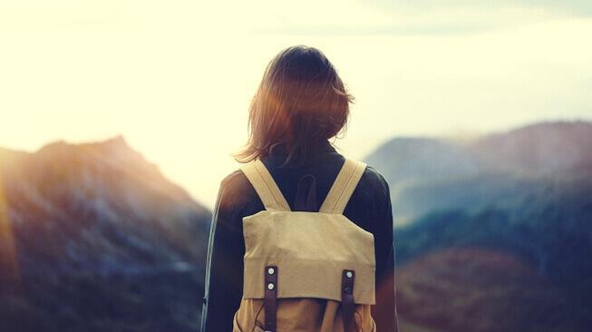 Frau mit Rucksack schaut auf Berge