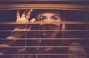 Erlernte Hilflosigkeit - Eine Frau spreizt ihre Finger hinter einer Jalousie, um dadurch ein Sichtfenster zu bekommen.