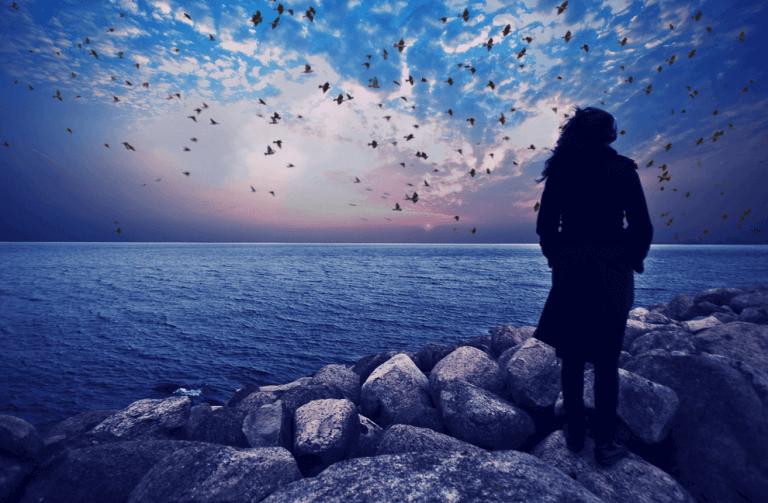 Eine Frau schaut auf den friedlichen Ozean. Der Himmel ist mit wenigen Wolken bedeckt.