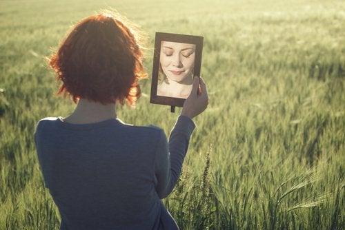 Eine Frau sitzt auf einem Feld und schaut sich selbst im Spiegel an.