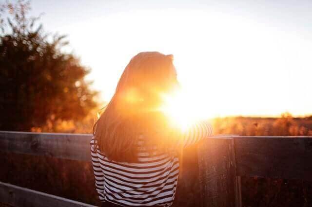Eine Frau steht an einem Holzzaun. Sie schaut sich den Sonnenuntergang an.