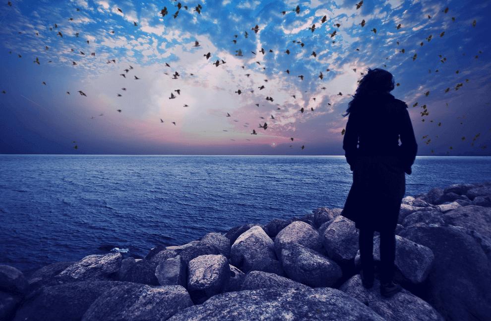 Frau schaut auf's Meer hinaus