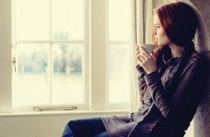 Richtige Pausen machen - Frau sitzt am Fenster