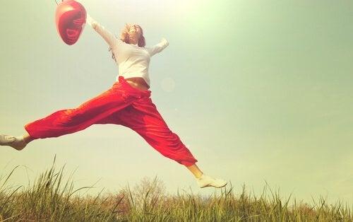 Eine Frau springt auf einer Wiese