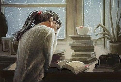 Eine Frau liest vor einem Stapel Bücher