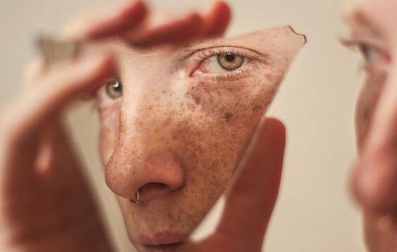 Mann sieht sein Gesicht in einer Scherbe