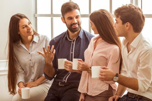 Vier Freunde trinken zusammen Kaffee und plaudern