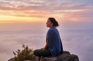 Pablo Neruda und die Stille - Frau meditiert über den Wolken