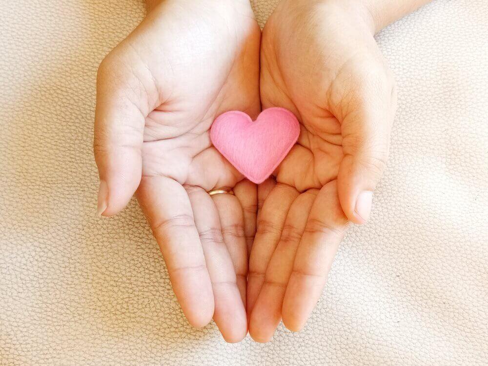 Zwei Hände halten ein rosa Herz aus Stoff.