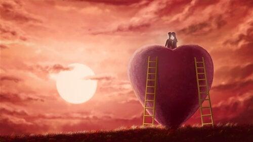 Paar sitzt auf einem großen Herz und schaut gen Horizont
