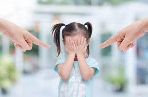 Toxische Eltern zeigen mit dem Finger auf ihr Kind