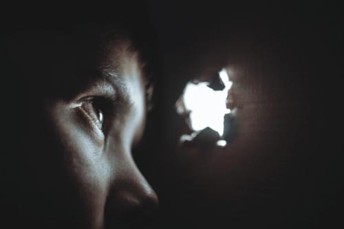 Kind guckt durch ein Loch