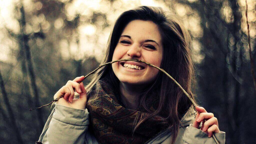 Eine lachende Frau spielt mit einem Zweig.