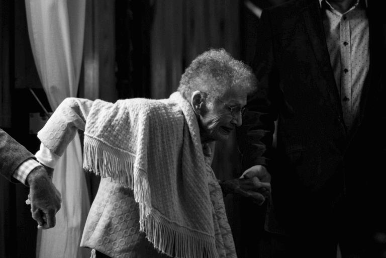Alte Frau geht an den Händen zweier Helfer