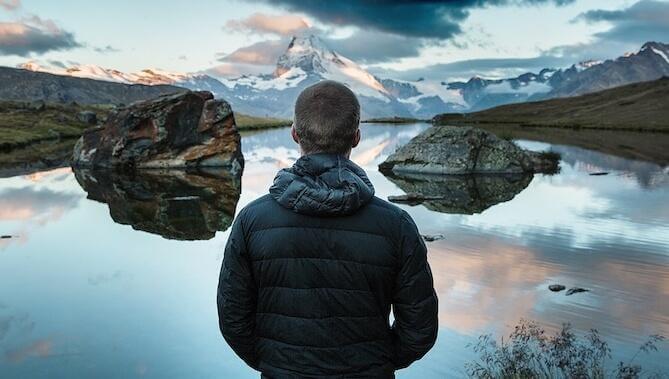 Mann schaut auf einen See