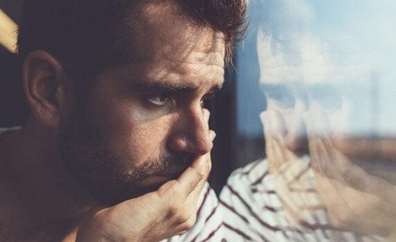Mann blickt traurig durch ein Fenster