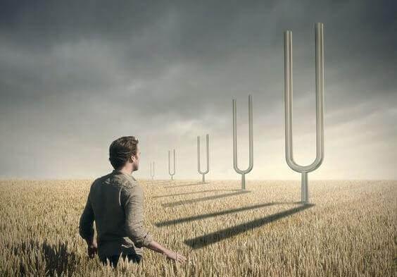 Mann steht in Getreidefeld und blickt auf fünf gigantisch große Stimmgabeln.