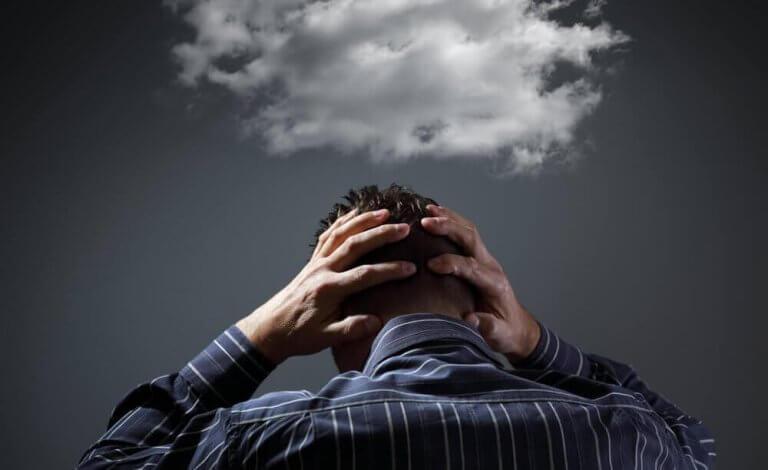 Ein Mann hält sich den Kopf, über dem eine Wolke schwebt.