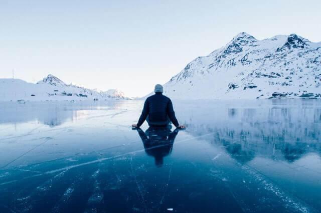Mann sitzt auf zugefrorenem See vor Bergen