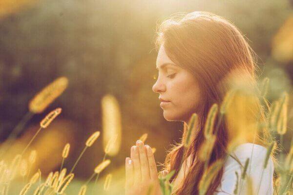 Frau meditiert im Blumenfeld