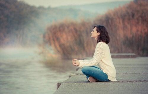 Eine Frau sitzt meditierend an einem friedlichen See.