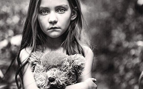 Ein trauriges Mädchen drückt ihren Teddybär.
