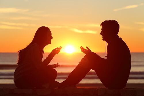 Ein Paar sitzt am Strand bei Sonnenuntergang und unterhält sich.