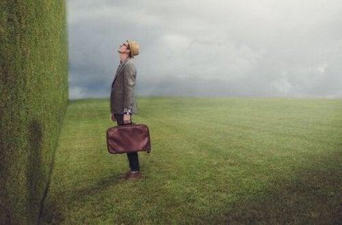 Mann, der vor einer Mauer aus Büschen steht