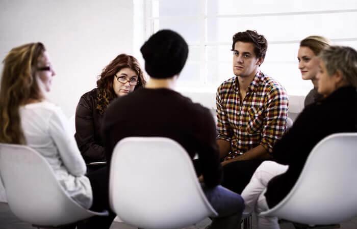 Im Kreis sitzende Selbsthilfegruppe tauscht sich aus.