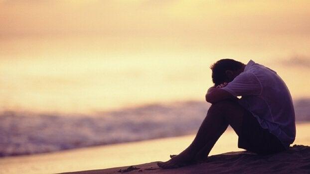 Trauriger Mann sitzt gebückt am Strand