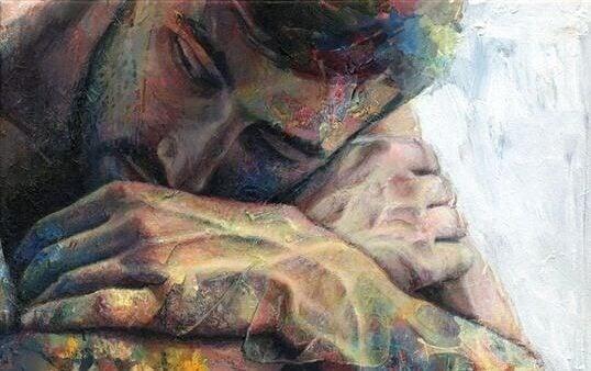 Ein Mann legt seinen Kopf auf seinen Armen ab. Er wirkt depressiv.