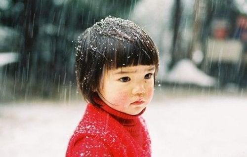 Was bleibt nach dem Tod der Eltern? - Trauriges Kind in roter Jacke steht im Schneeregen.