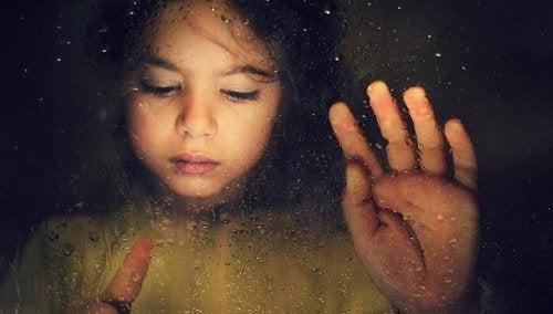 Ein trauriges Kind malt mit den Fingern auf einer verregneten Fensterscheibe.