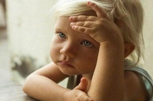 Ein kleines Kind stützt den Kopf auf den Händen ab, schaut besorgt