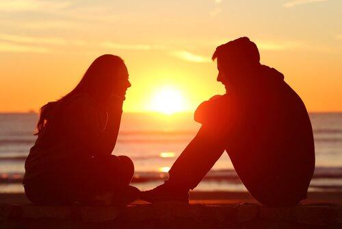 Zwei Freunde sitzen am Strand bei Sonnenuntergang und reden