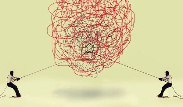 Zwei Menschen ziehen jeweils am Ende eines Seiles, das in einem riesigen Knoten verworren ist.