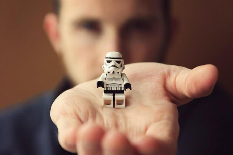 Mann, der einen Lego-Stormtrooper in der Hand hält