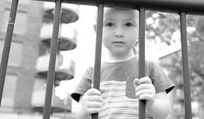 Junge, der hinter einem Gitter steht