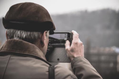 Älterer Herr, der mit dem Smartphone ein Foto macht