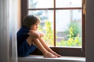 Überfürsorgliche Eltern - trauriger Junge, der am Fenster sitzt